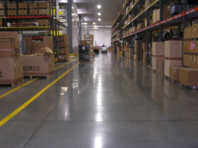 A polished concrete floor runs between two rows of shelves in a Volkswagen parts warehouse in WI. Boxes are stacked high on both sides of the aisle.