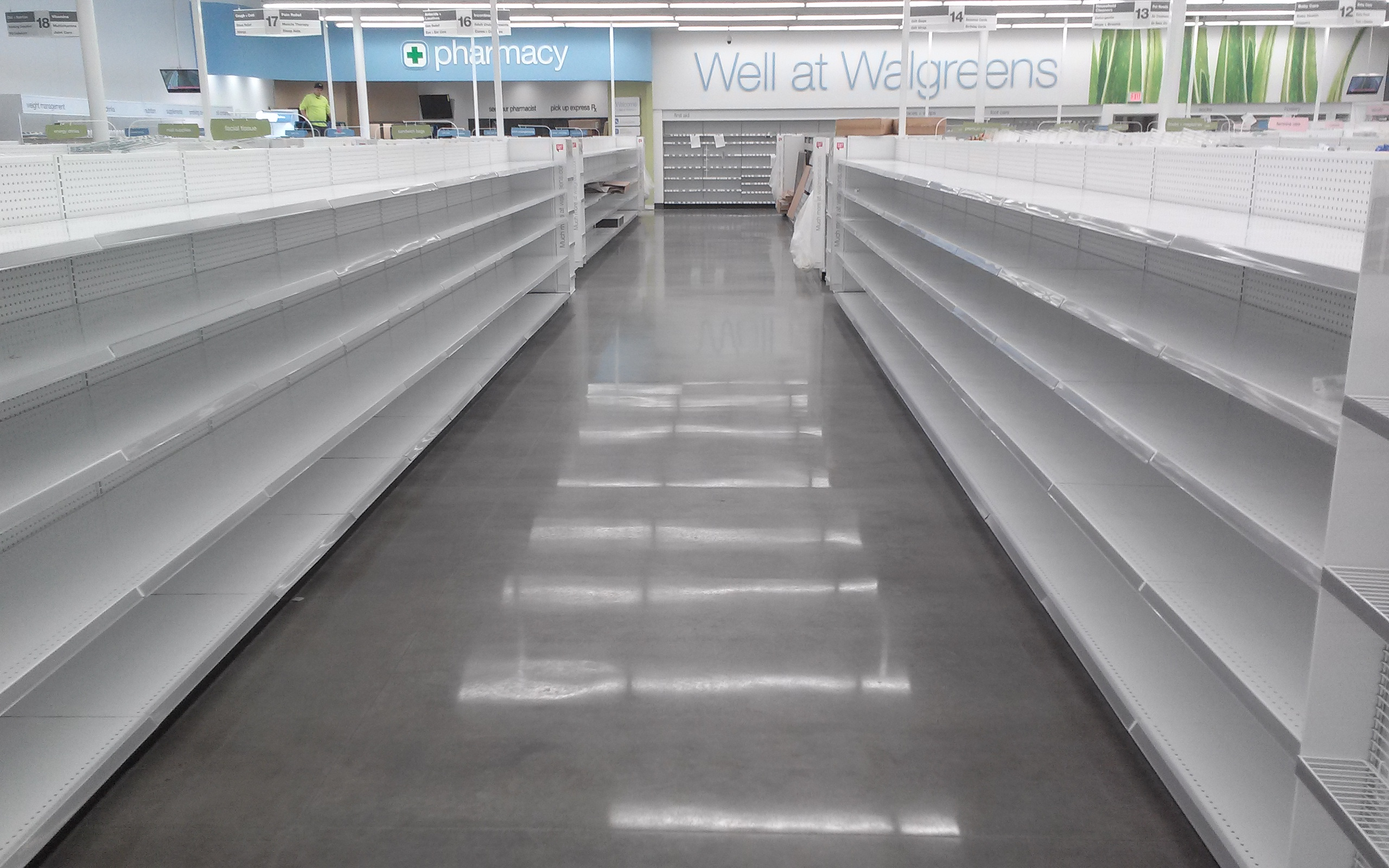 A polished cement floor aisle runs between two white, empty rows in a Walgreens.