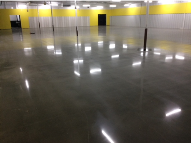 Lights shine on a dark grey polished concrete floor.