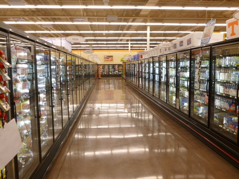 An earth-toned, polished concrete floor aisle runs between two rows of glass door refrigerators at a grocery store.