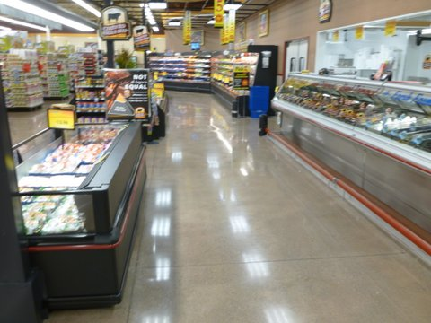 Concrete flooring supports displays in the meat department of a grocery store.