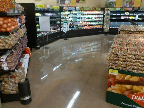 Produce displays sit on a polished cement floor at a grocery store.