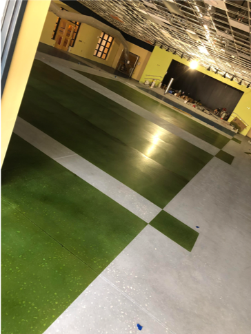 A green and white patterned polished concrete floor in a showroom.